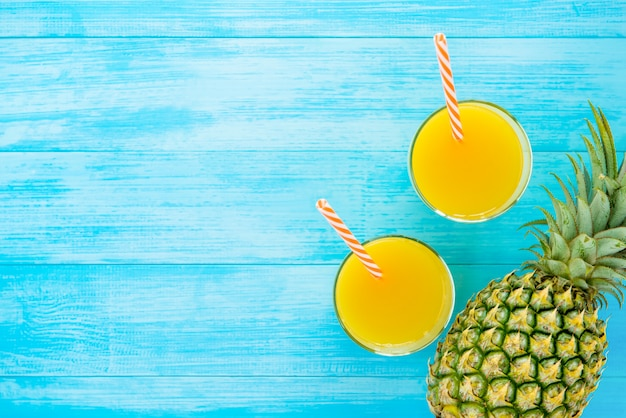 Orzeźwiające napoje na lato, słodki tropikalny sok ananasowy na jasnoniebieskim tle drewna