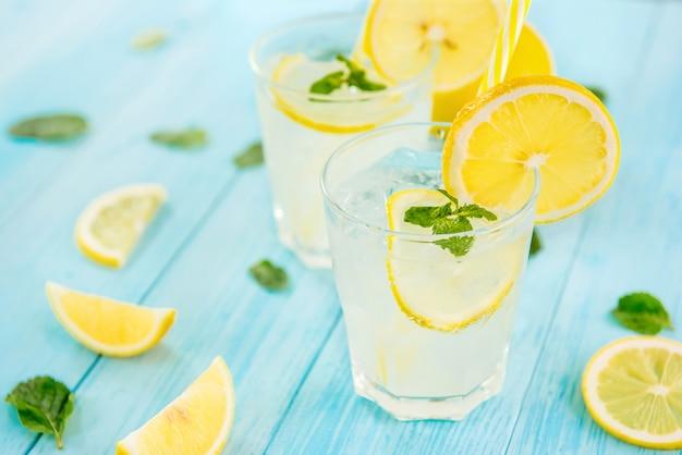 Orzeźwiające napoje na lato, zimny sok z lemoniadą z pokrojonymi w plasterki świeżymi cytrynami