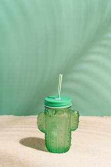Orzeźwiający kieliszek z napojem w kształcie kaktusa i słomy na piasku na tropikalnej plaży z cieniem liści palmy kokosowej latem