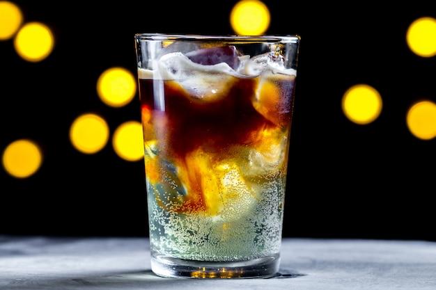 Orzeźwiający koktajl z kostkami lodu i bąbelkami sody na powierzchni świateł. mrożona kawa. napoje zimne i gazowane