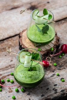 Orzeźwiający koktajl zielony ogórek jarmuż w szklance. koktajl detox, świeży zielony groszek, ogórek, rzodkiew, szpinak i limonka. obraz pionowy. widok z góry.
