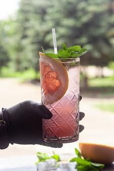 Orzeźwiający letni koktajl z plasterkiem grejpfruta. napój alkoholowy paloma. ozdobiony gałązką mięty i kostkami lodu.