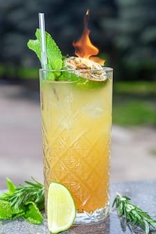Orzeźwiający letni koktajl z plasterkiem limonki. napój alkoholowy. przyozdobiony gałązką mięty i kostkami lodu. w barze.