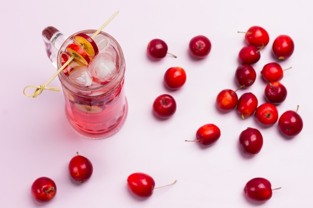 Orzeźwiający letni napój jabłkowy z lodem w szkle. pokrojone jabłka na patyku. małe czerwone jabłka na różowym tle. widok z góry.