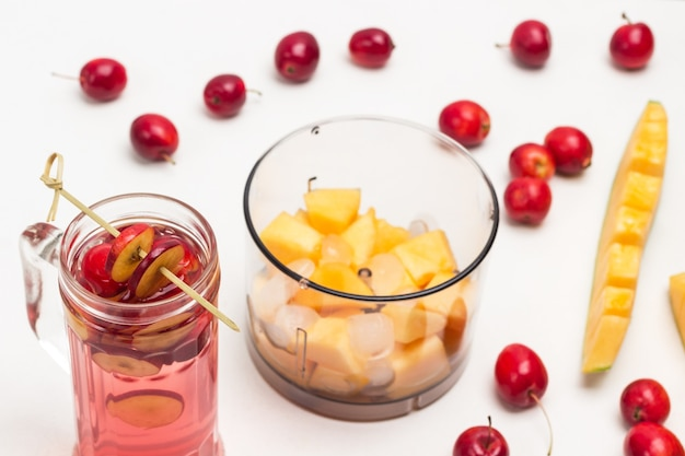 Orzeźwiający letni napój jabłkowy z lodem w szkle. pokrojone jabłka na patyku. melon pokrojony w słoik blendera. małe czerwone jabłka i kawałek melona na stole. białe tło. widok z góry.