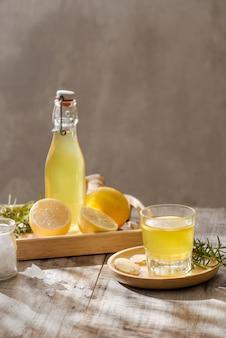 Orzeźwiający letni napój z cytryną, imbirem, rozmarynem i lodem na rustykalnym drewnianym stole, kopia przestrzeń