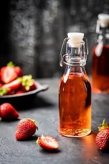 Orzeźwiający letni napój z truskawką w butelce na ciemnym tle