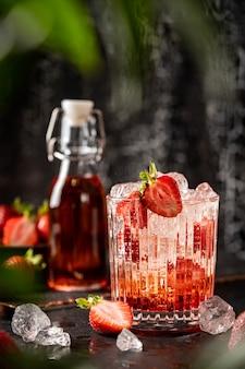 Orzeźwiający letni napój z truskawkami i lodem w szklance na ciemnym tle