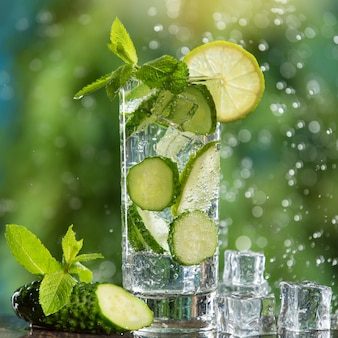 Orzeźwiający napój gazowany w szklance z limonką, miętą i plasterkami świeżego ogórka