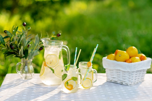 Orzeźwiający napój lemoniadowy w dzbanku i słoikach z cytrynami, świeżą miętą i lodem z koszem z cytrynami i kumkwatem na stole ogrodowym. letni piknik na świeżym powietrzu. miękka selektywna ostrość.