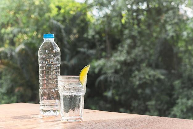 Orzeźwiający napój szklanka wody z plasterkiem limonki na drewnianym stole.