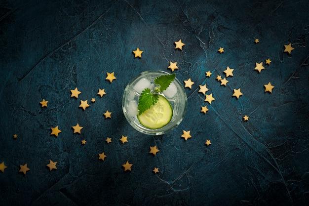 Orzeźwiający napój z lodem, ogórkiem i miętą na ciemnoniebieskim tle z gwiazdami. koncepcja klub nocny, nocne życie, impreza, pragnienie. leżał płasko, widok z góry