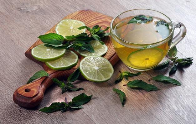 Orzeźwiający napój z miętą i limonką. filiżankę herbaty miętowej z limonką na drewnianym stole.