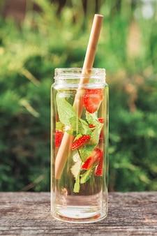 Orzeźwiający napój z miętą i truskawkami w ekologicznej stylowej butelce