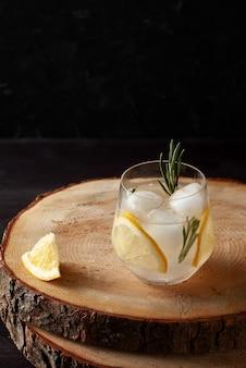 Orzeźwiający napój z rozmarynem cytrynowym i lodem na ciemnym drewnianym tle