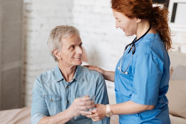 Orzeźwiający napój. zmotywowana charyzmatycznie, uważna kobieta dbająca o dobre samopoczucie pacjenta, serwując mu szklankę wody podczas regularnych wizyt w domu