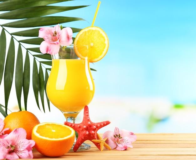 Orzeźwiający pomarańczowy koktajl na stole na plaży