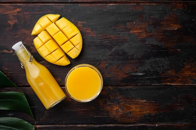 Orzeźwiający zestaw soku z tropikalnego mango, na starym ciemnym tle drewnianego stołu, widok z góry płaski, z kopią miejsca na tekst