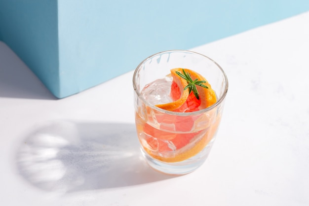 Orzeźwiający zimny napój w szklance z plasterkiem grejpfruta i kostkami lodu na białym stole