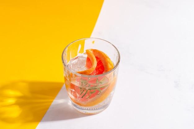Orzeźwiający zimny napój w szklance z plasterkiem grejpfruta i kostkami lodu