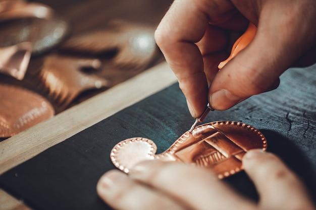 Osadzanie wzorów na rzeźbie buta z brązu