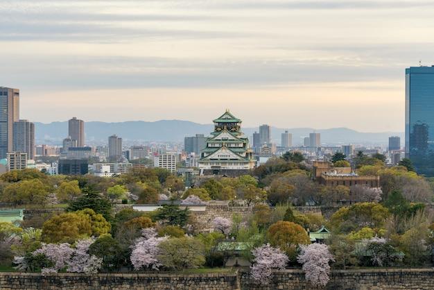 Osaka kasztel z czereśniowym okwitnięciem i osaka centrum biznesowym dyktatem w tle atosaka, japonia.