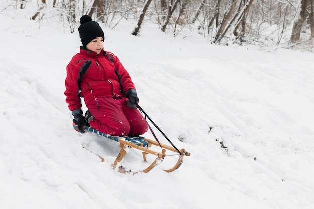 Osamotniona chłopiec cieszy się sanie jedzie w zimie