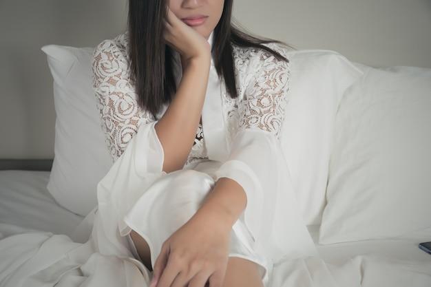 Osamotniona i przygnębiona smutna kobieta w koszula nocna z rękami na twarzy.
