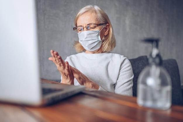 Osamotniona smutna starsza starsza kobieta w twarzy medycznej masce używa ręcznego antybakteryjnego ciekłego sanitizer z laptopem w domu samoizolaci kwarantanną podczas pandemii koronawirusa covid19. zostań w domu