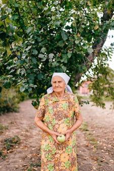 Osamotniona stara kobieta stoi w ogródzie przed jabłonią z zielonym jabłkiem w rękach. nieszczęśliwa smutna kobieta z pomarszczonym portretem skóry. 90-letnia dama