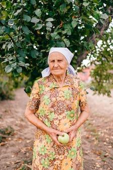 Osamotniona stara kobieta stoi w ogródzie przed jabłonią z zielonym jabłkiem w rękach