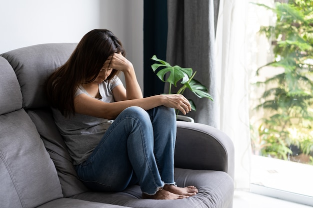 Osamotniony młody azjatykci kobiety felling deprymujący i stresujący się w żywym pokoju w domu, negatywny emoci pojęcie