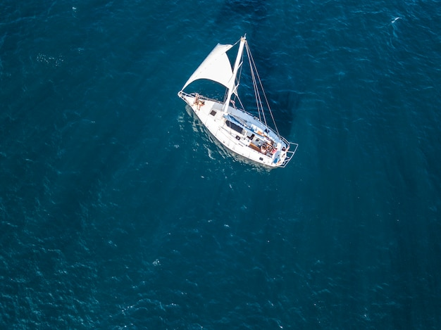 Osamotniony odosobniony jacht pod żaglem z wysokim masztem iść w spokojnym dennym powietrznym odgórnym widoku