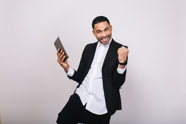 Osiąganie świetnych wyników w pracy, sukcesy w karierze przystojnego młodzieńca w białej koszuli i wyrażającej radość czarnej marynarce. stylowy biznesmen, nowoczesny, radosny, uśmiechnięty.