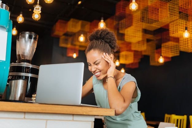 Osiąganie wyników. ciemnowłosa kobieta czuje się bardzo szczęśliwa i wzruszona po osiągnięciu efektów w swojej pracy