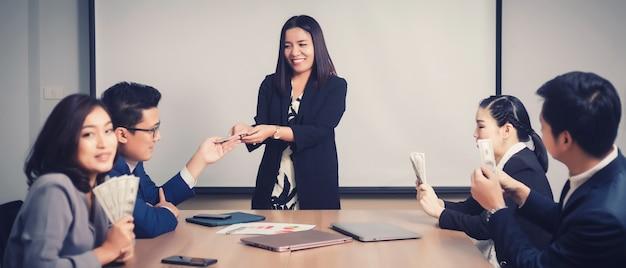 Osiągnięcie zespołu biznesowego i zdobądź banknoty dolarów od szefa podczas spotkania