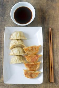 Osiem gotowanych lub smażonych jiaozi lub gedzy podanych z sosem sojowym.
