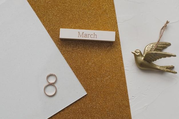 Osiem wykonanych z dwóch złotych obrączek i napisu marzec. kartka z życzeniami na 8 marca