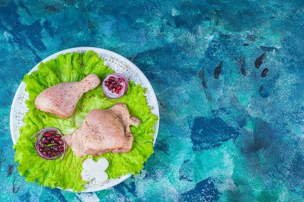 Osłonki granatu, liście sałaty z krążkiem cebuli obok mięsa z kurczaka na talerzu