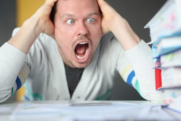 Osłupiały mężczyzna trzyma głowę i patrzy na stos folderów. trudne terminy w koncepcji biznesowej