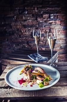 Ośmiornica z sałatką jarzynową na białym talerzu z aperitifem. kulinarne serwowanie posiłków w restauracjach.