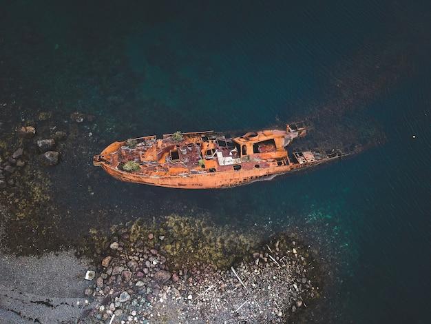 Ośniedziała stara łódź w morzu