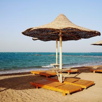 Ośniedziałe teksturowane parasole na pustej plaży rano
