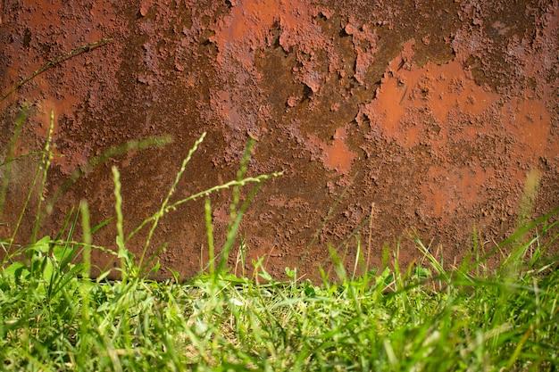 Ośniedziały brown stary metalu tło i obniżona granica zielona trawa. tekstura korozji
