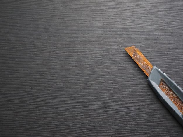 Ośniedziały duchowny nóż na ciemnym stole.