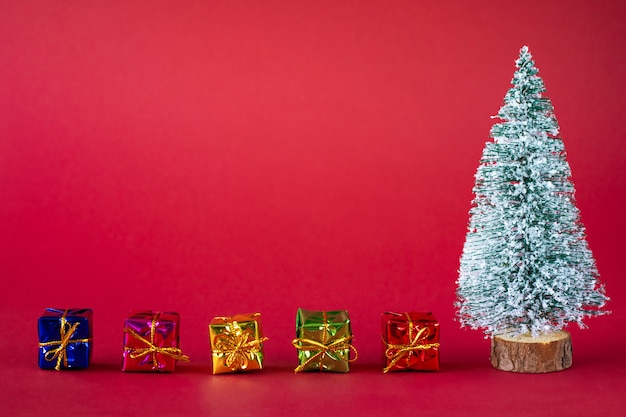 Ośnieżona choinka i jasne, wielokolorowe pudełka z prezentami.
