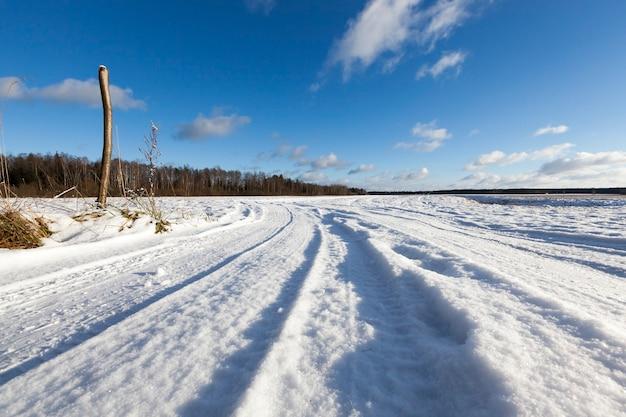 Ośnieżona droga w sezonie zimowym. widoczne ślady samochodu. niebo z chmurami w tle. po lewej stronie znajduje się kawałek złamanego drzewa - pień