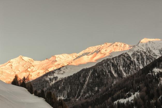 Ośnieżona góra świeci słońce