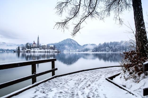 Ośnieżone drewniane molo nad alpejskim jeziorem bled zimowy krajobraz podróże słowenia europa