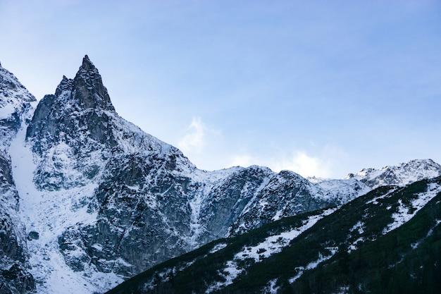 Ośnieżone góry w alpach. chmury latające w pobliżu szczytów gór
